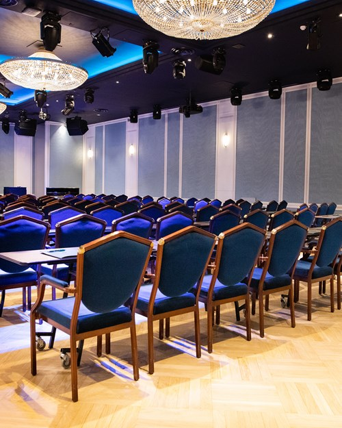 Cinema setup in Haakon Salen, with dark blue chairs and counters in each row. Light blue decorated walls and chandeliers hanging from the ceiling