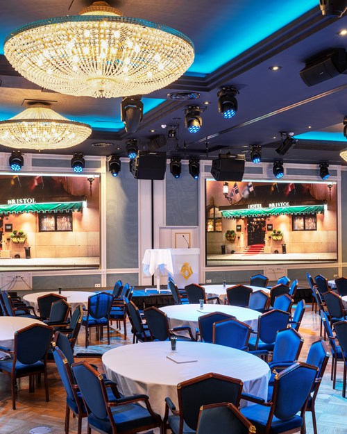 Round tables covered with white linens , two LCD screens and chandeliers hanging from the ceiling