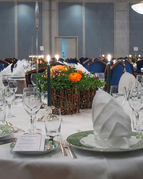 Nicely decorated table, with white linens and crystal chandeliers hanging from the ceiling