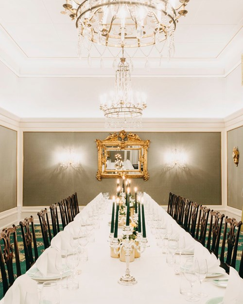 Dining table covered with white tablecloths, candlesticks, flower arrangements. In the background stands a piano and a gold-framed mirror. Two large chandeliers hanging from the ceiling