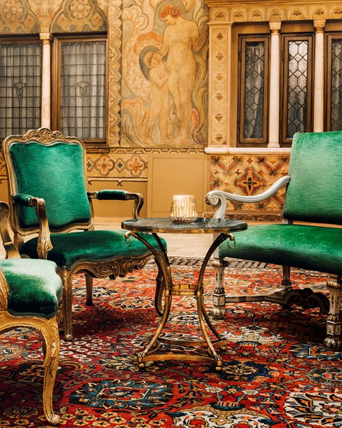 Dignified and spacious ballroom with wallpaintings and dark green furniture