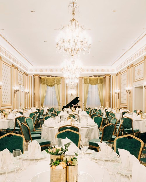 Bright banqueting area with decorated tables, green delicate chairs and chandeliers hanging from the ceiling